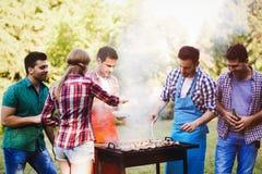 Amis heureux appréciant la partie de barbecue Images stock