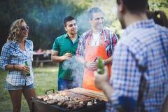Amis heureux appréciant la partie de barbecue Photographie stock libre de droits