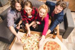 Amis heureux appréciant la pizza Images libres de droits