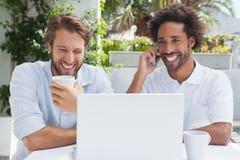 Amis heureux appréciant le café ainsi que l'ordinateur portable Image libre de droits