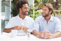 Amis heureux appréciant le café ensemble Image stock