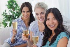 Amis heureux appréciant le champagne regardant ensemble l'appareil-photo Photographie stock