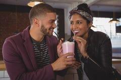 Amis heureux appréciant le milkshake en café Photographie stock libre de droits