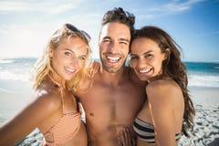 Amis heureux appréciant le moment sur la plage Photographie stock libre de droits
