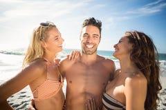 Amis heureux appréciant le moment sur la plage Photos stock