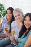 Amis heureux appréciant le vin blanc regardant ensemble l'appareil-photo Photos stock
