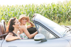 Amis heureux appréciant le voyage par la route dans le convertible Photographie stock libre de droits