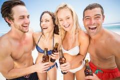 Amis heureux appréciant sur la plage Photo stock
