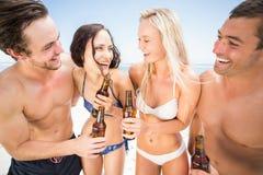 Amis heureux appréciant sur la plage Photographie stock