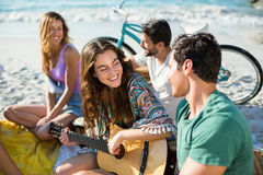 Amis heureux appréciant tout en se reposant à la plage Photos stock