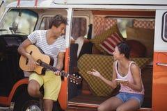 Amis heureux appréciant tout en se reposant dans le camping-car Images stock