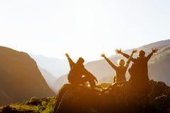 Amis heureux au coucher du soleil dans la gamme de montagnes Photo stock