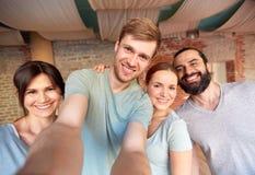 Amis heureux au studio ou au gymnase de yoga prenant le selfie Photographie stock