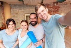 Amis heureux au studio ou au gymnase de yoga prenant le selfie Image libre de droits