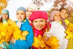 Amis heureux avec de beaux groupes de feuilles Photographie stock