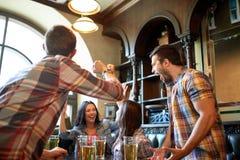 Amis heureux avec de la bière célébrant à la barre ou au bar Images libres de droits