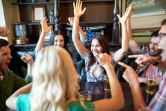 Amis heureux avec de la bière célébrant à la barre ou au bar Image stock