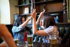 Amis heureux avec de la bière célébrant à la barre ou au bar Image libre de droits