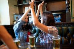 Amis heureux avec de la bière célébrant à la barre ou au bar Photographie stock libre de droits