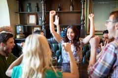 Amis heureux avec de la bière célébrant à la barre ou au bar Images stock
