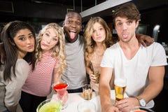 Amis heureux avec de la bière et des cocktails collant la langue Photos libres de droits