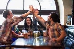 Amis heureux avec de la bière faisant la haute cinq au bar Images libres de droits