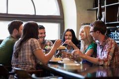 Amis heureux avec de la bière mangeant à la barre ou au bar Photos stock