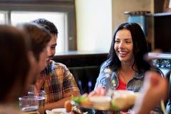 Amis heureux avec de la bière mangeant à la barre ou au bar Photos libres de droits