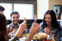 Amis heureux avec de la bière mangeant à la barre ou au bar Photo stock