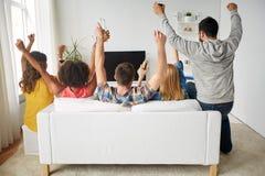 Amis heureux avec de la bière regardant la TV à la maison Photos stock