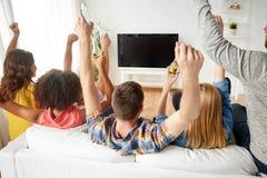 Amis heureux avec de la bière regardant la TV à la maison Images stock