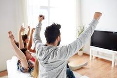 Amis heureux avec de la bière regardant la TV à la maison Image libre de droits