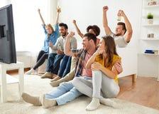 Amis heureux avec de la bière regardant la TV à la maison Image stock