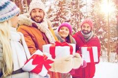 Amis heureux avec des boîte-cadeau dans la forêt d'hiver Photo stock