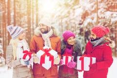 Amis heureux avec des boîte-cadeau dans la forêt d'hiver Image stock