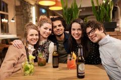 Amis heureux avec des boissons à la barre ou au café Images stock