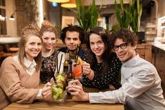 Amis heureux avec des boissons à la barre ou au café Photographie stock