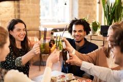 Amis heureux avec des boissons à la barre ou au café Image libre de droits