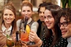 Amis heureux avec des boissons à la barre ou au café Photos stock