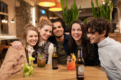 Amis heureux avec des boissons à la barre ou au café Photo stock