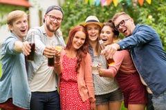Amis heureux avec des boissons à la réception en plein air d'été Image libre de droits