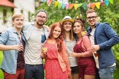Amis heureux avec des boissons à la réception en plein air d'été Photos stock