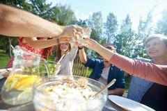 Amis heureux avec des boissons à la réception en plein air d'été Image stock