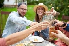 Amis heureux avec des boissons à la réception en plein air d'été Photo libre de droits