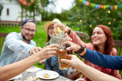 Amis heureux avec des boissons à la réception en plein air d'été Photos libres de droits