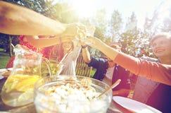 Amis heureux avec des boissons à la réception en plein air d'été Photographie stock