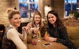 Amis heureux avec des boissons au restaurant Photos stock