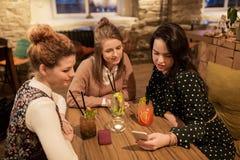 Amis heureux avec des boissons au restaurant Images stock