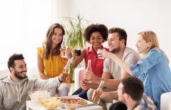 Amis heureux avec des boissons ayant la partie à la maison Images libres de droits