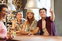 Amis heureux avec des boissons dirigeant le doigt à la barre Image libre de droits